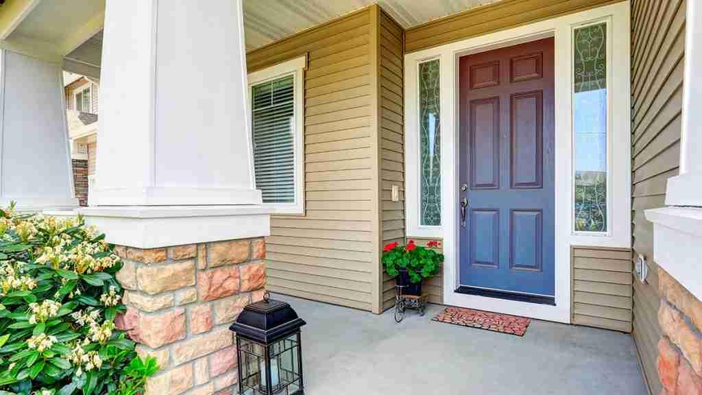 Porta d'ingresso anteriore con pavimento in cemento portico e vaso di fiori.